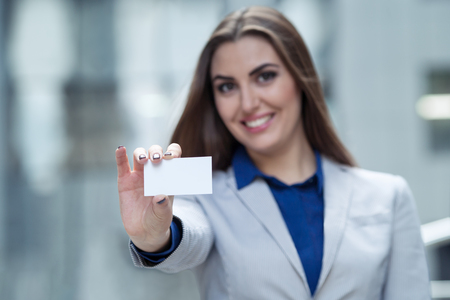 woman  hands a business card on a background of the business center
