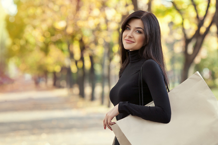 beautiful woman with shopping bag in park