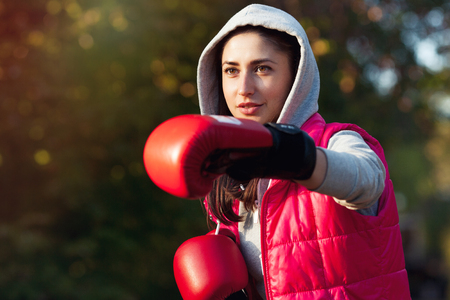 Portrait of a beautiful girl in red boxing gloves. Makes a punch hand
