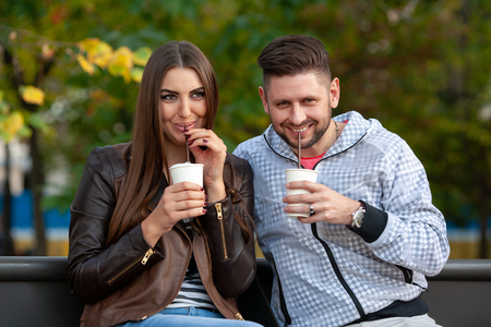 young couple drinking cocktails in the park, smiling at the camera