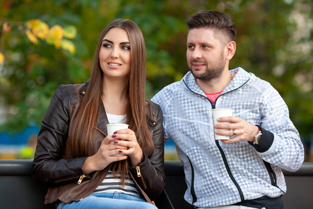 beautiful couple in a park drinking drinks, looking away