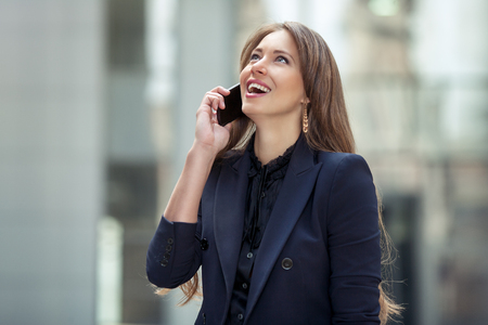 business woman talking on a cell phone on the background of the business center