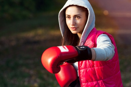 Beautiful girl is engaged in boxing at sunset. Close-up
