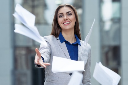 business woman throwing papers on the background of the business center