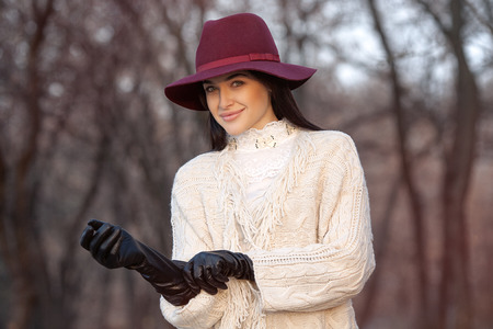 portrait of beautiful girl in hat and leather gloves