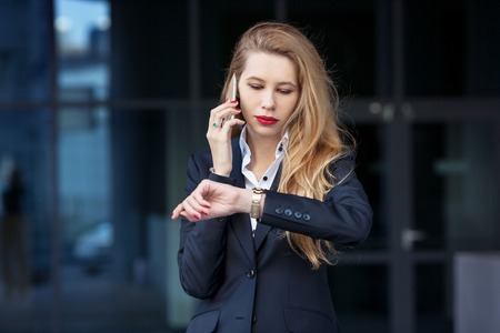 business woman speaks by phone and looks at her watch