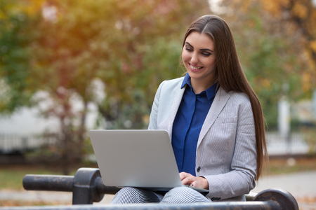 beautiful young businesswoman working on laptop in the park