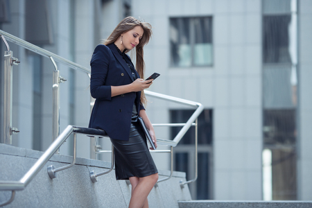 beautiful businesswoman with mobile on the background of the business center