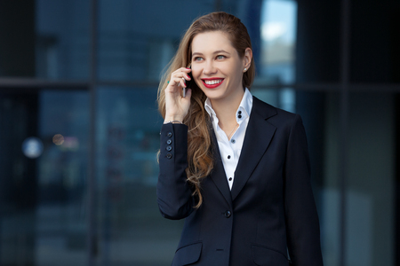 business woman speaks by phone on the background of the business center