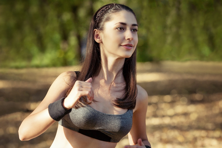 Girl in sport on the forest background. Likes to run