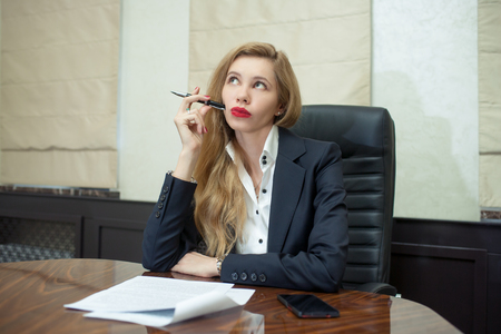 Businesswoman think looking up to empty copy space, young attractive business woman think, idea, hold folder pen on chin. concept pondering in modern office Stock Photo
