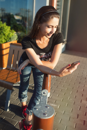 beautiful girl stands near a cafe, reads news in the phone at sunset 免版税图像