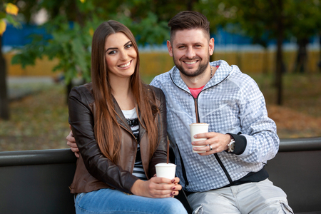 happy modern couple drinking coffee in the park. Look at the camera 免版税图像