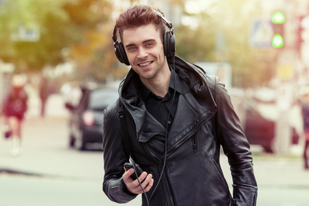 man in headphones on the street. Standing with phone in hand 免版税图像