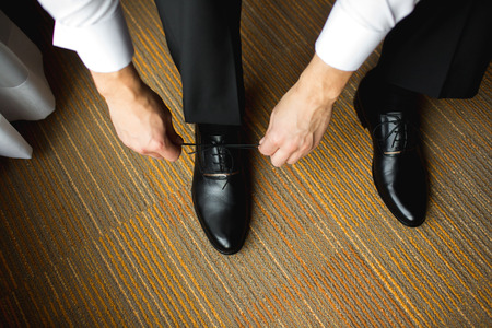 formal dressing: The Groom dressing up with classic, elegant shoes. Stock Photo