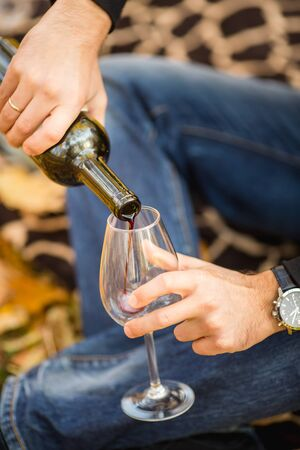 Man pours red wine in glass at the  picnic