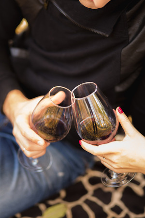 Two glasses of the red wine in the hands, picnic theme