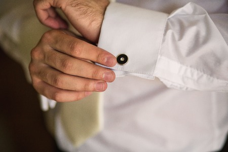 cuffs: groom in the morning on the wedding day buttoning cuffs his hands on his suit