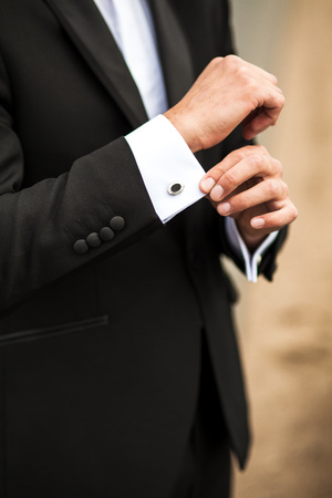 young  cuffs: groom in the morning on the wedding day buttoning cuffs his hands on his suit