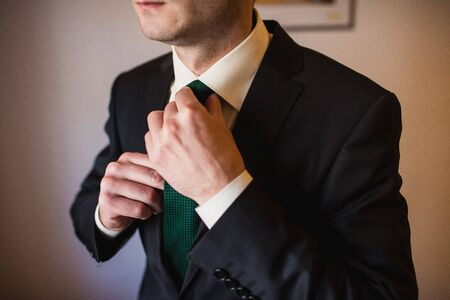 graduation suit: Groom in the morning on the wedding day set  the tie straight