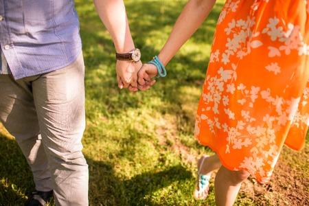 manos entrelazadas: joven la mano y caminar en el parque Foto de archivo