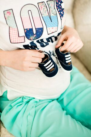 Pregnant woman holding small baby shoes relaxing at home on couch Zdjęcie Seryjne
