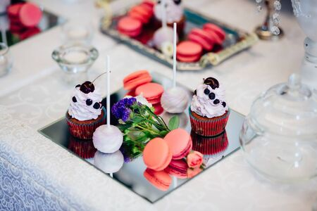 Variety of tasty appetizing sweet desserts with cream, berries and pastry on the grand wedding table.
