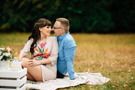 sweetly: A pregnant beautiful woman with her handsome husband sweetly resting outdoors in the autumn on picnic. Stock Photo