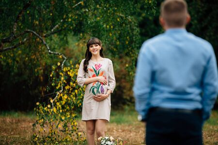 Beautiful pregnant woman is standing lovely on the green lawn with her hand on belly and looking at her handsome husband in autumn park.
