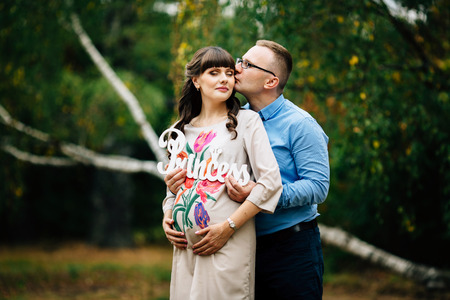 gestation: Pregnant woman and her handsome husband lovely hugging on nature and have picnic in park. Man kissing his young wife. They hold word Princess from wood in hands. Happy pregnant couple family. Stock Photo