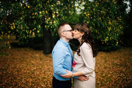 Young beautiful pregnant woman and her handsome husband kissing lovely in the autumn park. Relationships. Stock Photo