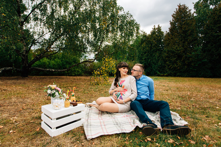 A pregnant beautiful woman with her handsome husband sweetly resting outdoors in the autumn park on picnic. Zdjęcie Seryjne