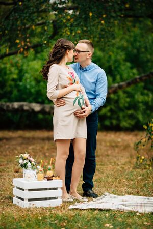 Pregnant beautiful woman and her handsome stylish husband lovely relaxing, hugging on nature and have picnic in autumn park. Happy pregnant couple family. Healthy pregnancy.