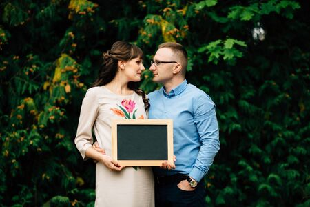 Expecting pregnant happy stylish couple holding a blank charcoal board. They are lovely looking into each others eyes.