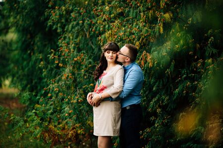 Pregnant woman and her handsome husband lovely hugging on nature and have picnic in park. Man kissing his young beautiful wife. Happy pregnant couple family.