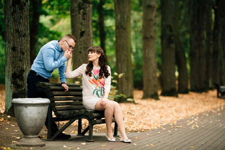 Beautiful pregnant stylish couple relaxing outside in the autumn park sitting on bench. Handsome husband kisses his wifes hand.