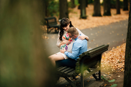 Beautiful pregnant stylish couple relaxing outside in the autumn park sitting on bench. They are lovely looking at belly. Zdjęcie Seryjne