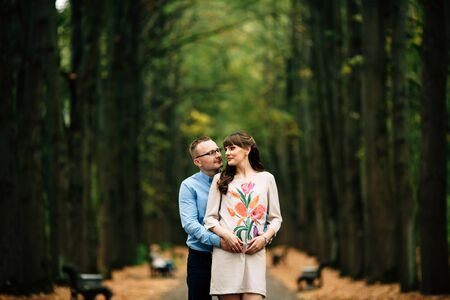Pregnant beautiful woman and her handsome husband lovely hugging in autumn alley. Happy pregnant couple family. Healthy pregnancy.