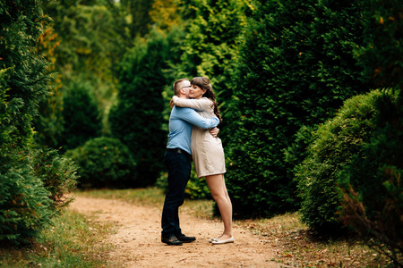Pregnant beautiful woman and her handsome husband lovely hugging in autumn park. Happy pregnant couple family. Healthy pregnancy.