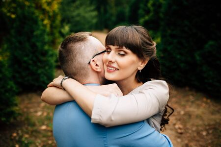 Happy and young pregnant couple lovely hugging in autumn park. Happy pregnant couple family. Healthy pregnancy. Zdjęcie Seryjne