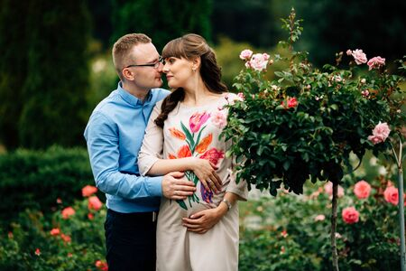 Pregnant beautiful woman and her handsome husband lovely hugging in park. Happy pregnant couple family. Healthy pregnancy.
