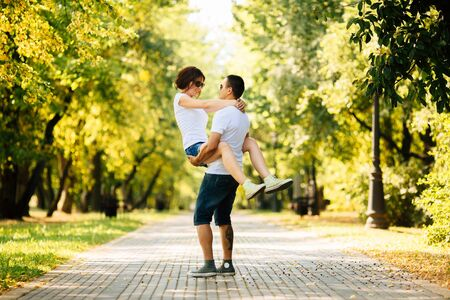 Hipster young couple in white T-shirts and denim shorts having fun together on a summers day in park.