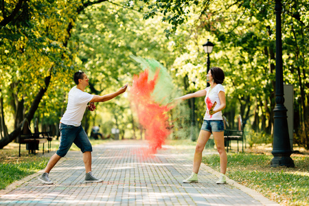 Young and beautiful, hipster couple funny playing in the park on holi color festival and throw each other with colour paint powder.  Dressed in white T-shirts and denim shorts.