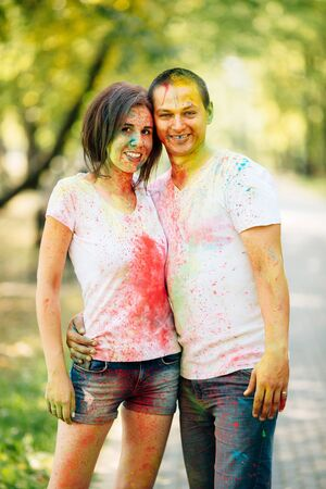 Young and beautiful, hipster couple laughing happily at camera in the park on holi color festival with colour paint powder. Dressed in white T-shirts and denim shorts.