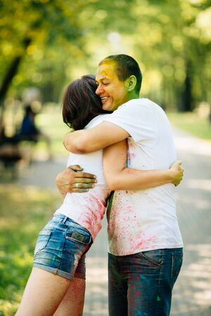 Young and beautiful, hipster couplehugging in the park on holi color festival with colour paint powder. Dressed in white T-shirts and denim shorts. Stockfoto