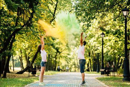 Young and beautiful, hipster couple funny playing in the park on holi color festival with colour paint powder. Dressed in white T-shirts and denim shorts.