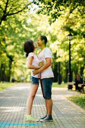 Beautiful, hipster couple funny playing in the park on holi color festival with colour paint powder. They are lovely looking into each other's eyes. Dressed in white T-shirts and denim shorts.