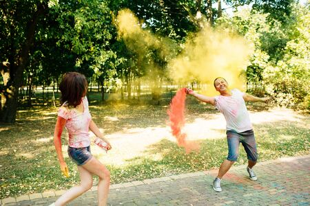 Young and beautiful, hipster couple funny playing in the park on holi color festival throw each other with colour paint powder. Dressed in white T-shirts and denim shorts.