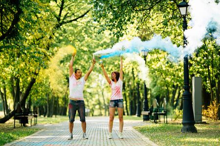 Young and beautiful, hipster couple funny playing in the park on holi color festival with colour paint powder and color smoke. Dressed in white T-shirts and denim shorts. Stockfoto