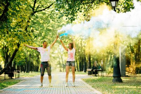 Young and beautiful, hipster couple funny playing in the park on holi color festival with colour paint powder and color smoke. Dressed in white T-shirts and denim shorts. Фото со стока